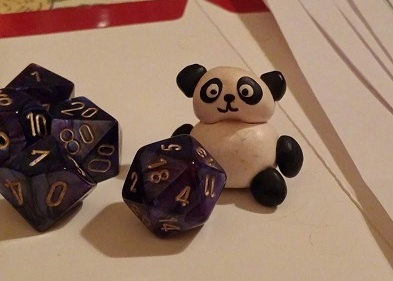A minifigurine shaped like a panda, and several D&D dice, including a D20 and two D10s.